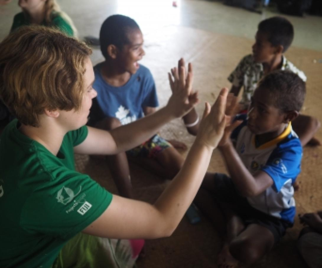 A volunteer in the South Pacific works with children and plays a game at a care center.